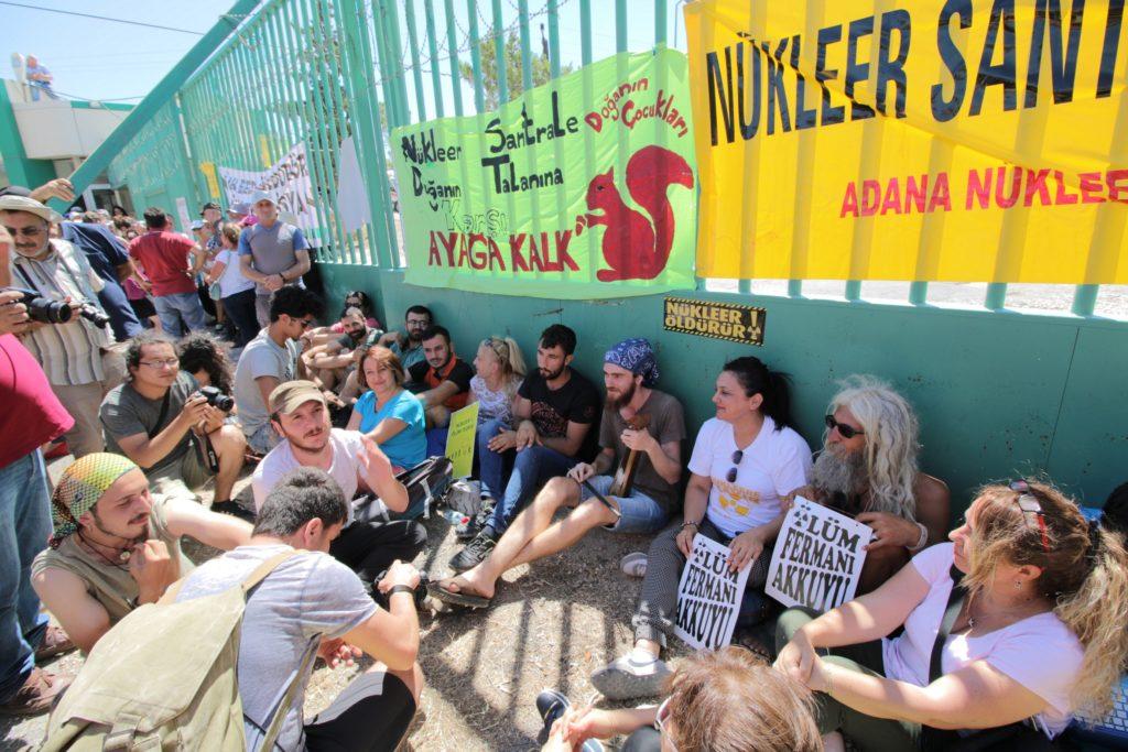 専門家の現地調査が行なわれる間、原発敷地前のゲートで抗議活動を行なう人々(7月11日、アックユ)
