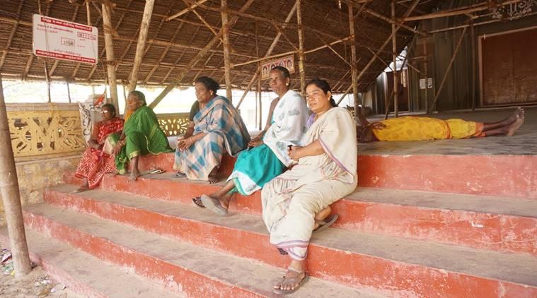 教会の敷地内にしつらえられた、わら屋根の集会場に座る女性たち